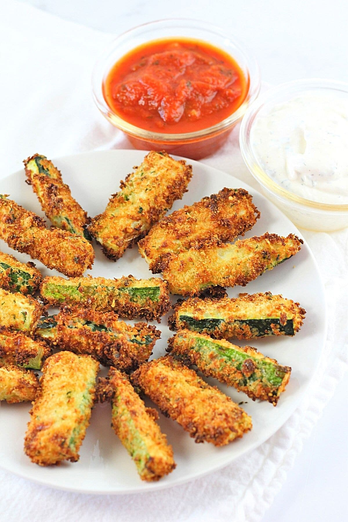 crispy breaded air fryer zucchini sticks on a white plate with small bowls of marinara sauce and ranch dip on the side