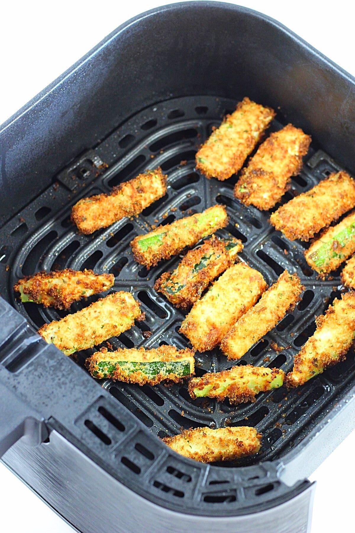 crispy breaded air fryer zucchini sticks in an air fryer basket