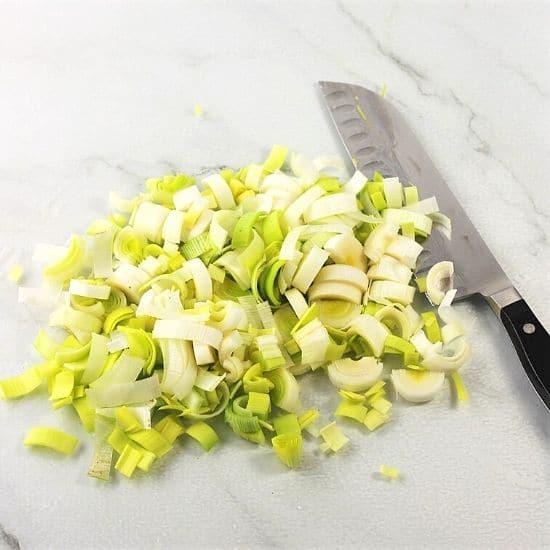 chopped leeks on a white surface with a knife