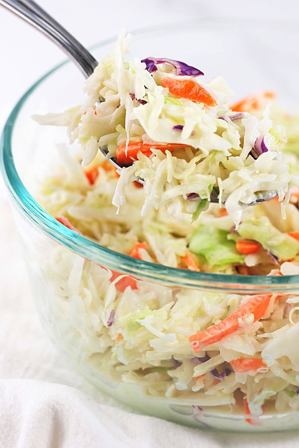 a bowl of classic creamy coleslaw with a spoonful being lifted out