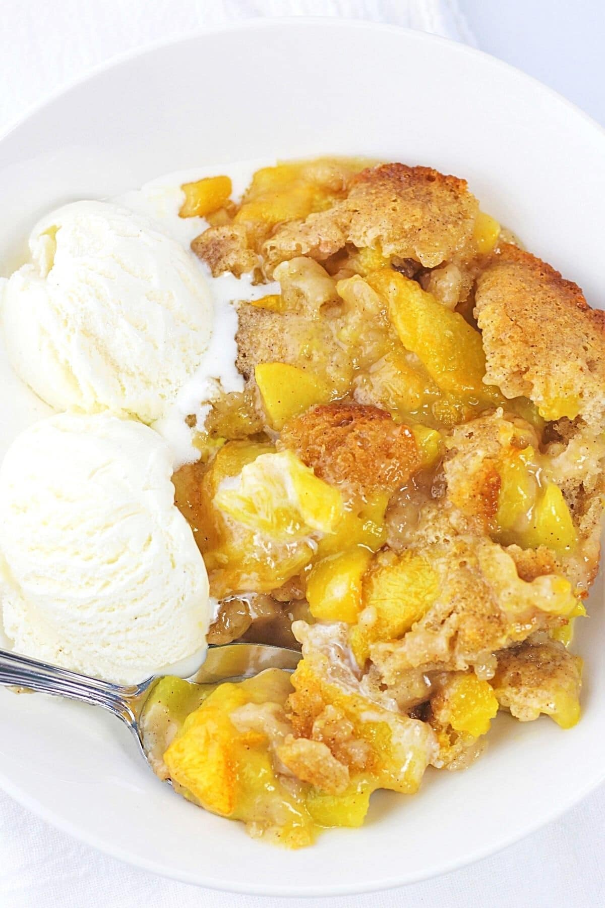 easy fresh peach cobbler in a bowl with 2 scoops of vanilla ice cream