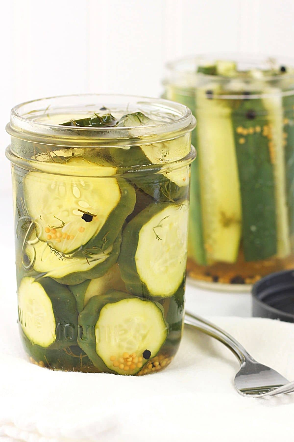 2 jars of garlic and dill 24-hour refrigerator pickles with a jar lid and fork on the side
