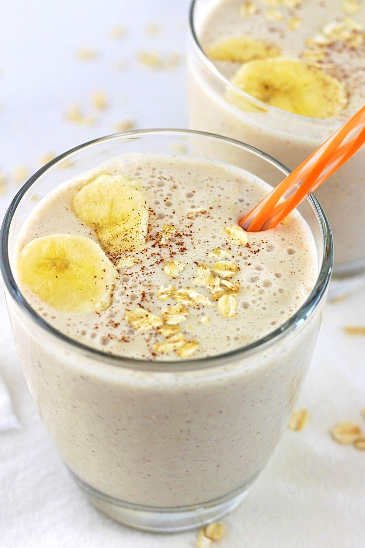 close-up of an oatmeal banana bread smoothie with a straw in it and a second smoothie in the background