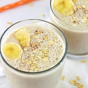 two oatmeal banana bread smoothies garnished with banana slices, oats and cinnamon with a straw in the background