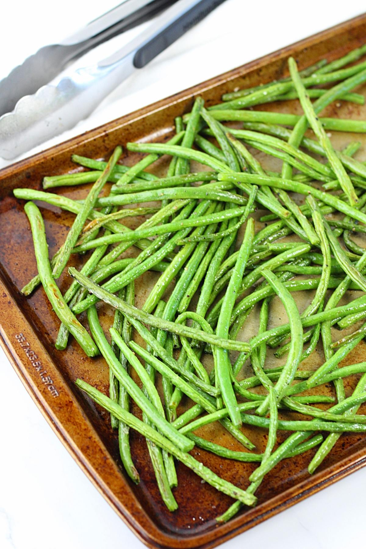 oven-roasted green beans on a baking sheet with tongs on the side
