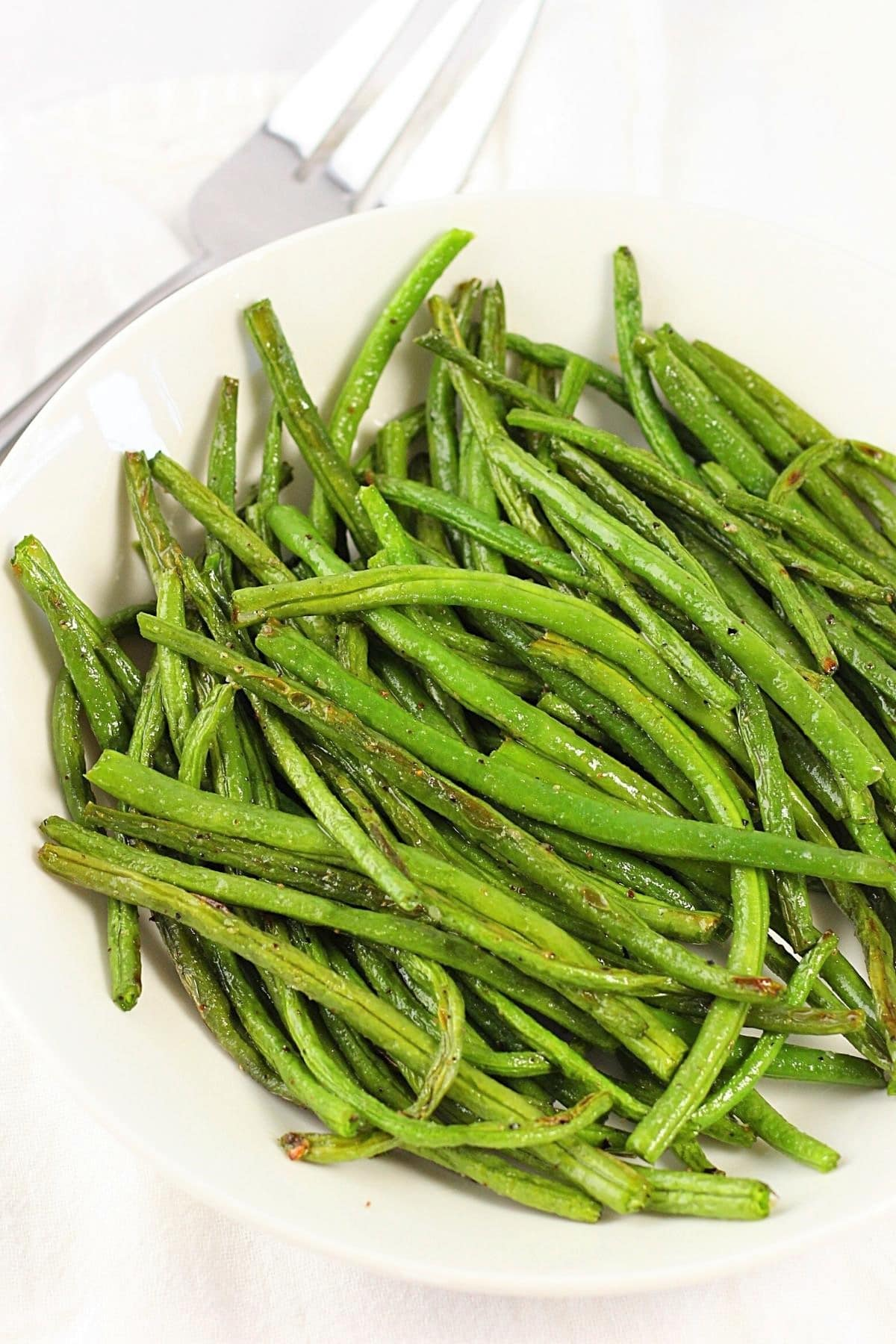 oven-roasted green beans on a white plate with a serving fork on the side