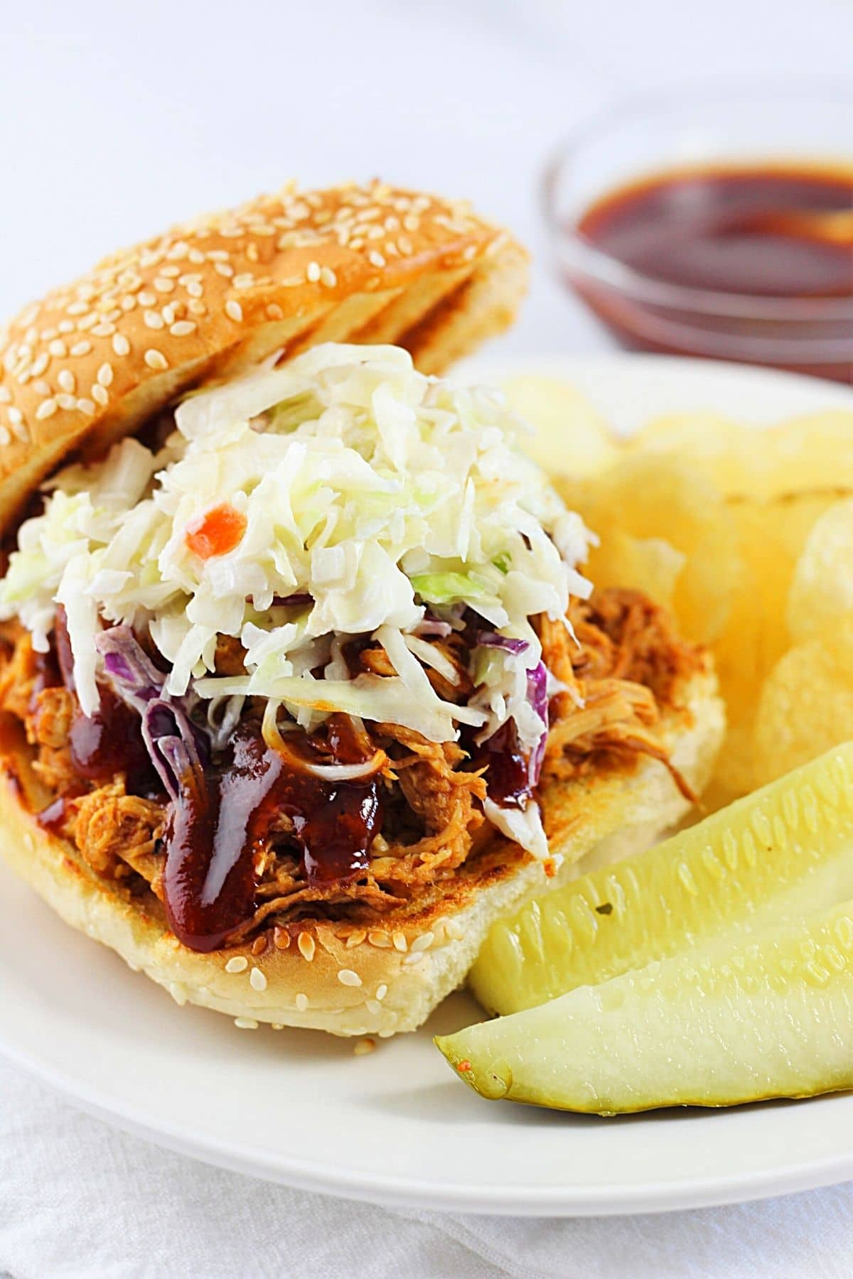 slow cooker bbq pulled chicken on a bun topped with barbecue sauce and coleslaw and potato chips and pickles on the side