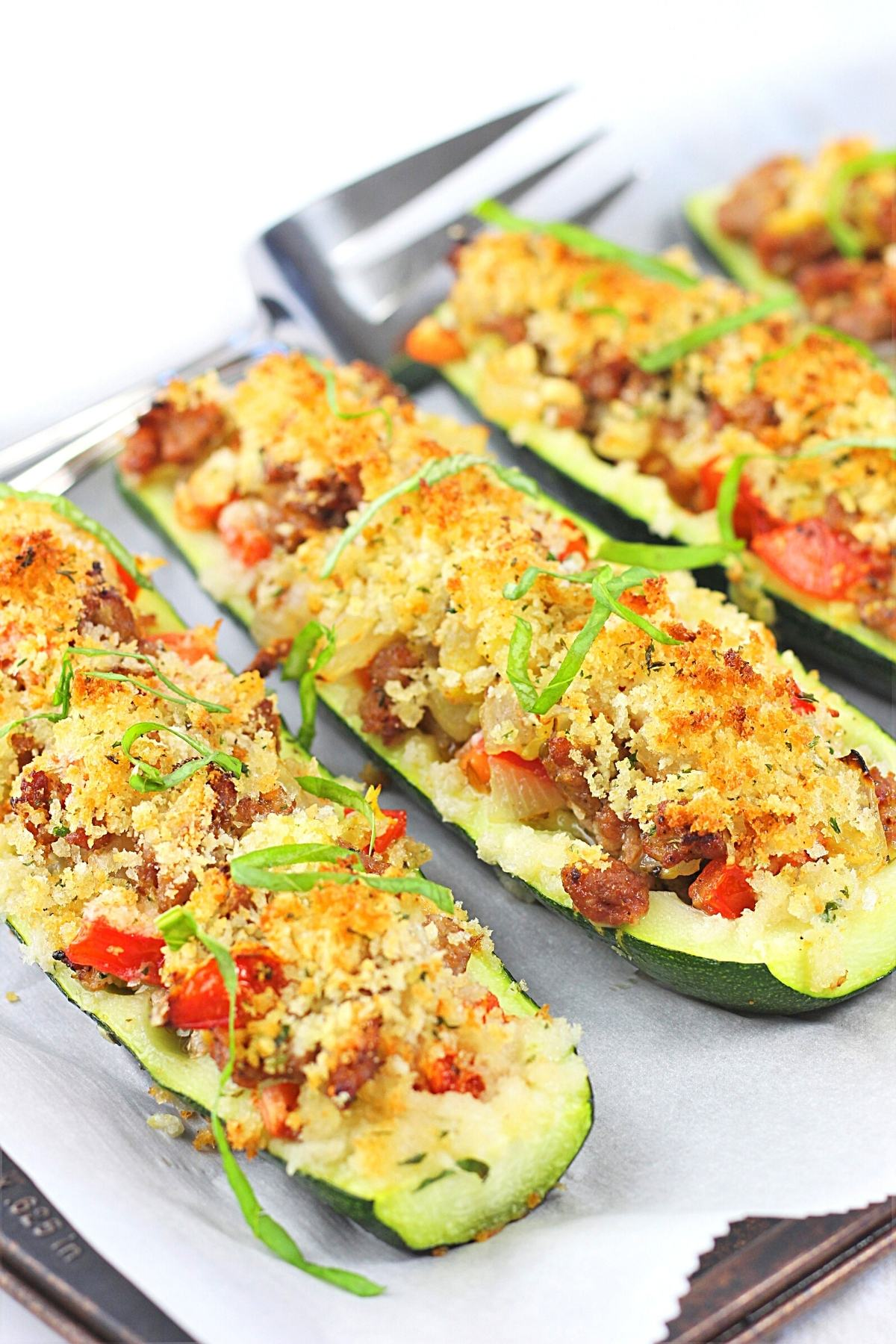 stuffed zucchini boats with sausage and tomatoes on a baking sheet sprinkled with basil with a serving fork on the side