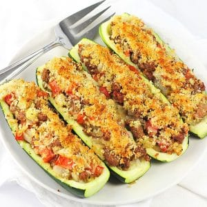 four stuffed zucchini boats on a white plate with a serving fork