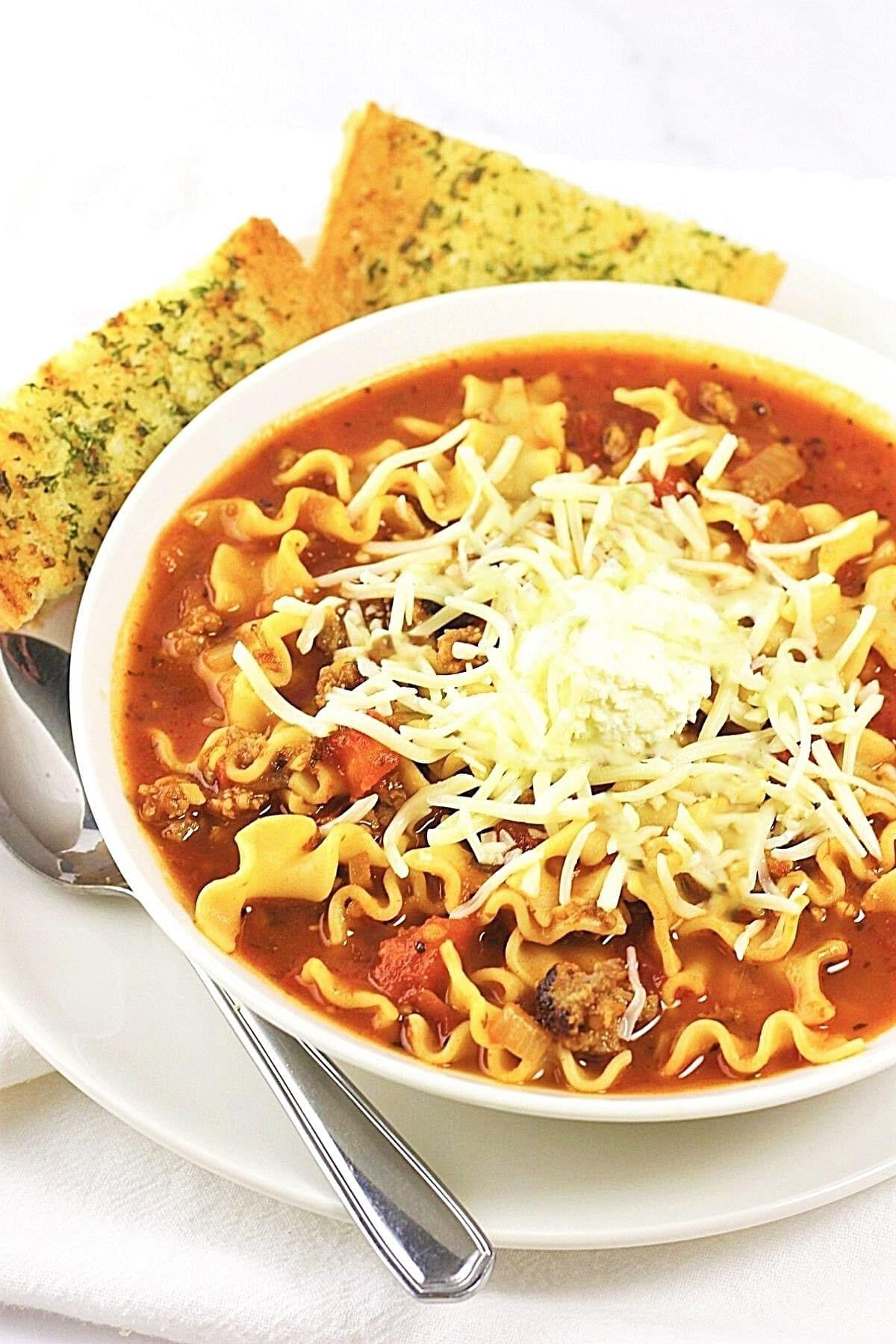 bowl of easy lasagna soup on a plate with a spoon and slices of garlic bread on the side