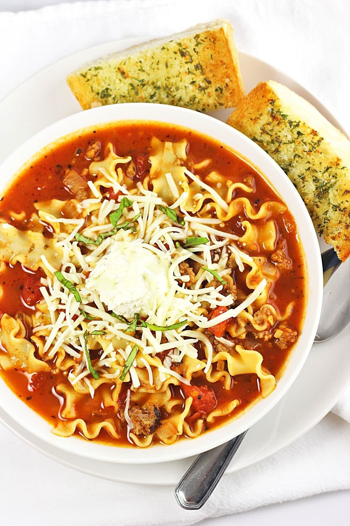 bowl of lasagna soup garnished with strips of basil with a spoon and pieces of garlic bread on the side