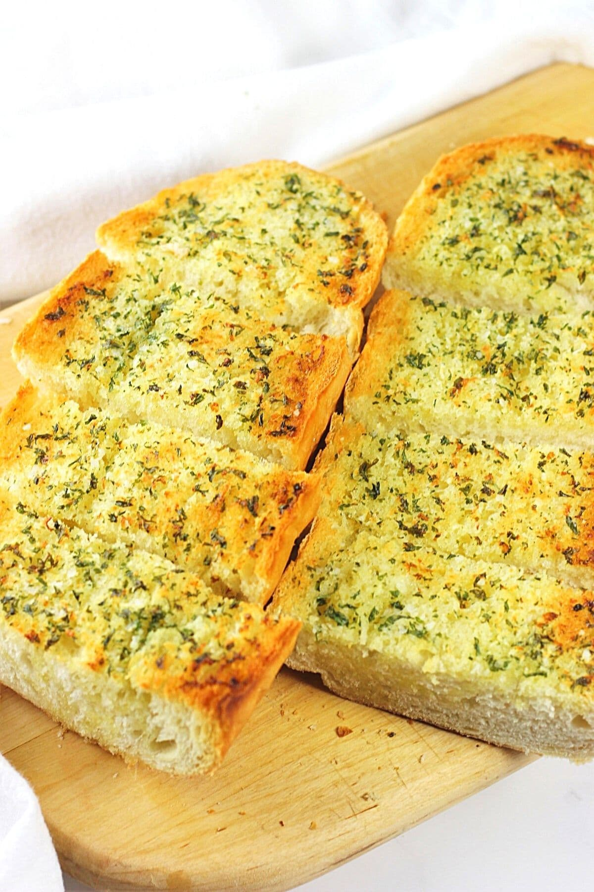homemade garlic bread on a cutting board with a napkin on the side