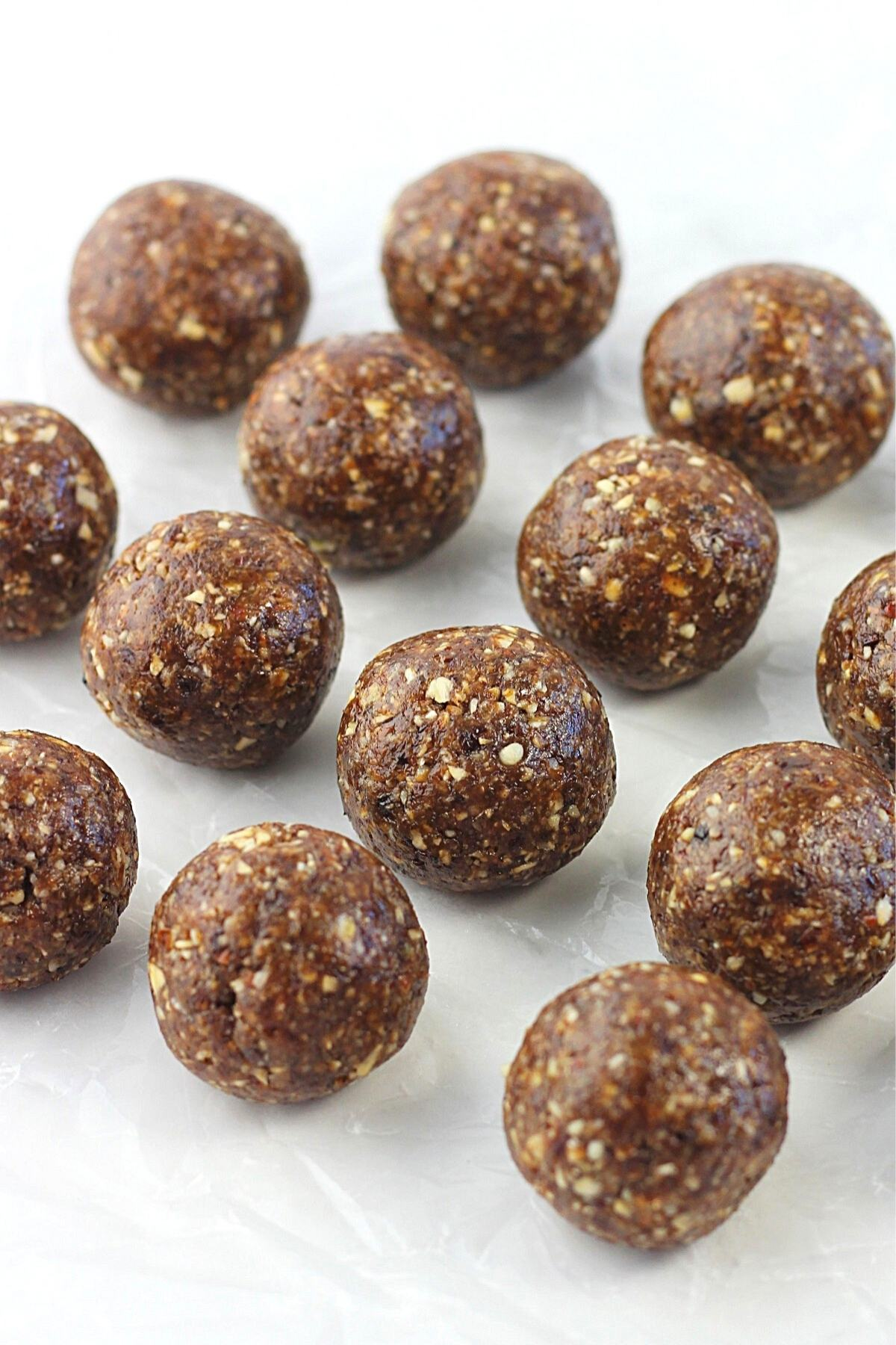 several oatmeal, raisin and pecan energy bites on a white surface