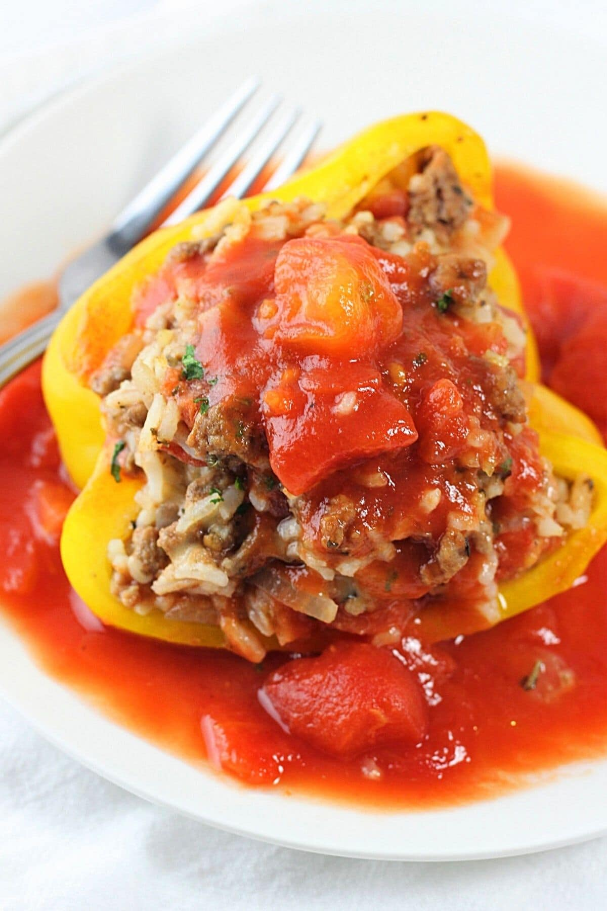 saucy stuffed bell pepper on a white plate with a fork with extra sauce on the plate and on top of the pepper