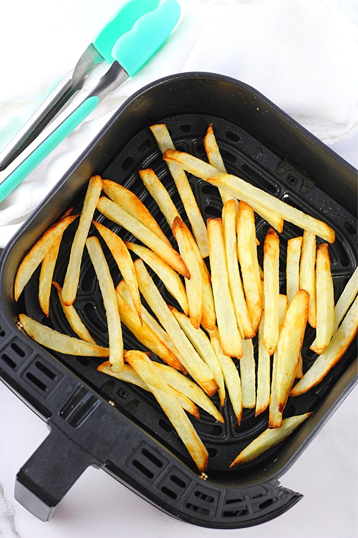 homemade French fries in an air fryer basket with a napkin and tongs on the side
