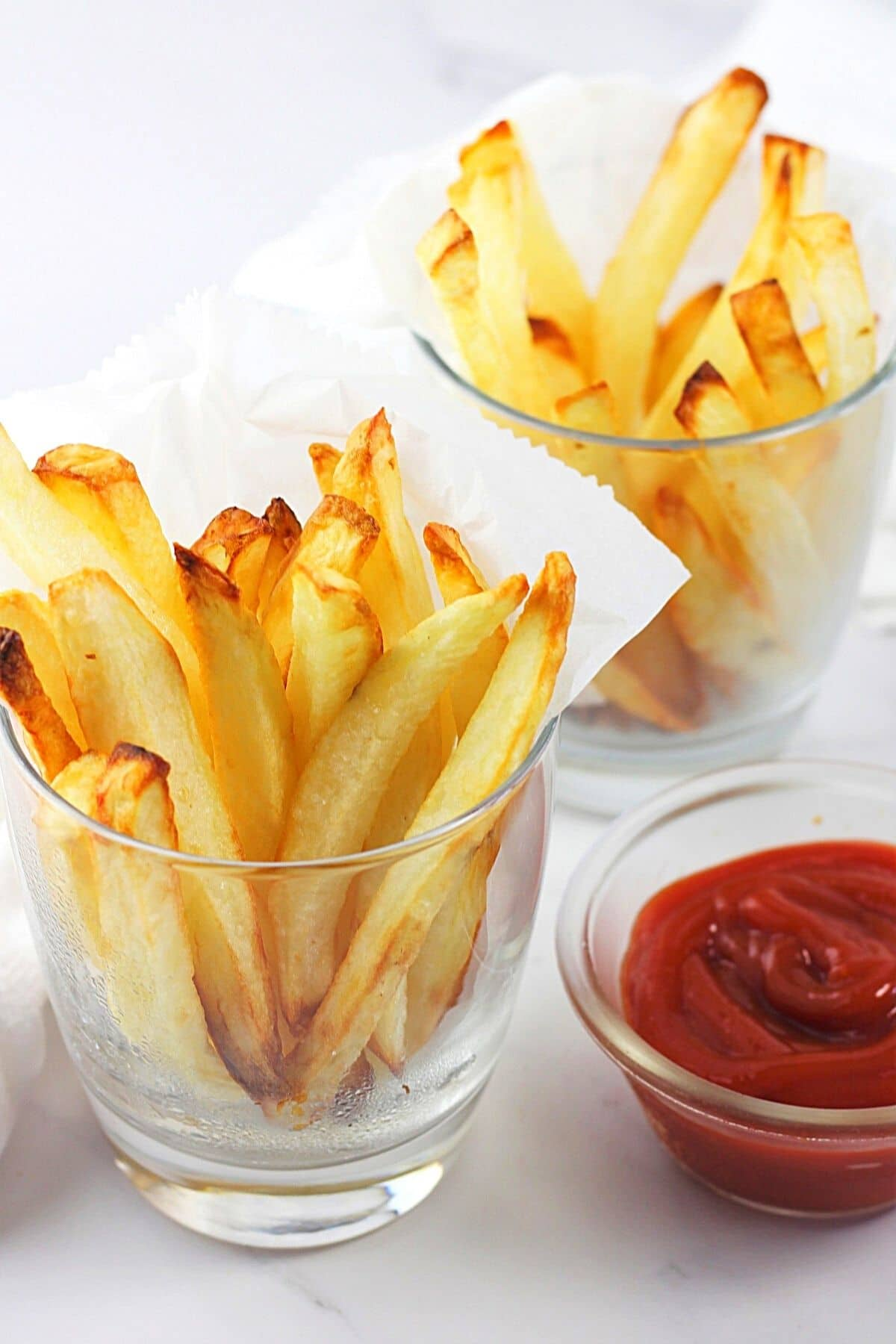 two glasses filled with air fryer homemade French fries and a small bowl of ketchup on the side