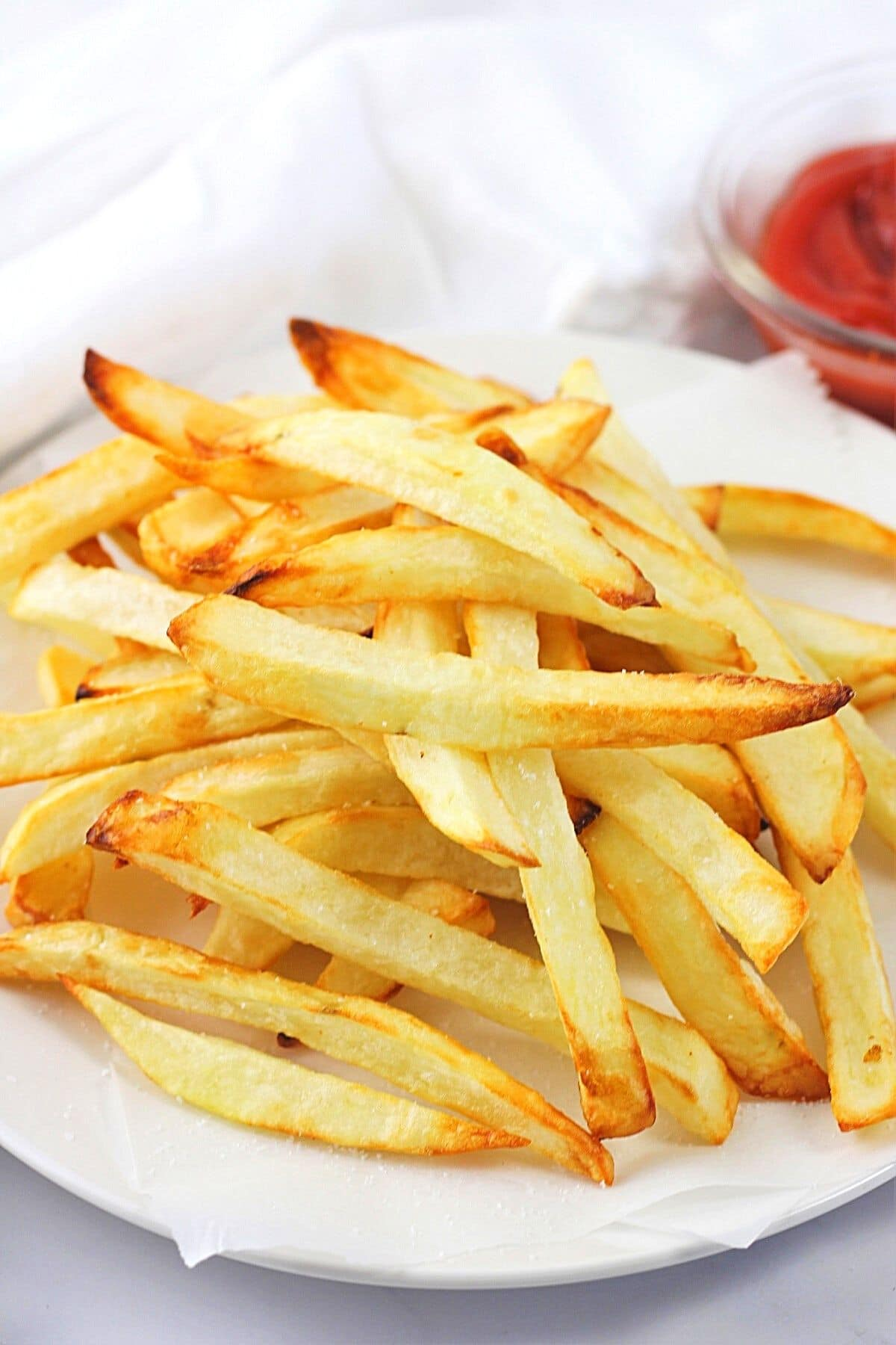 air fryer homemade French fries on a white plate with a small bowl of ketchup on the side
